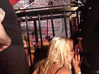 Kinky submissive blonde babe gets a cum shot while trapped in a cage