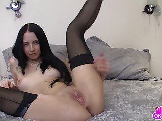 Lusty babe in stockings with long black hair shoves a violet dildo deep in her pussy.